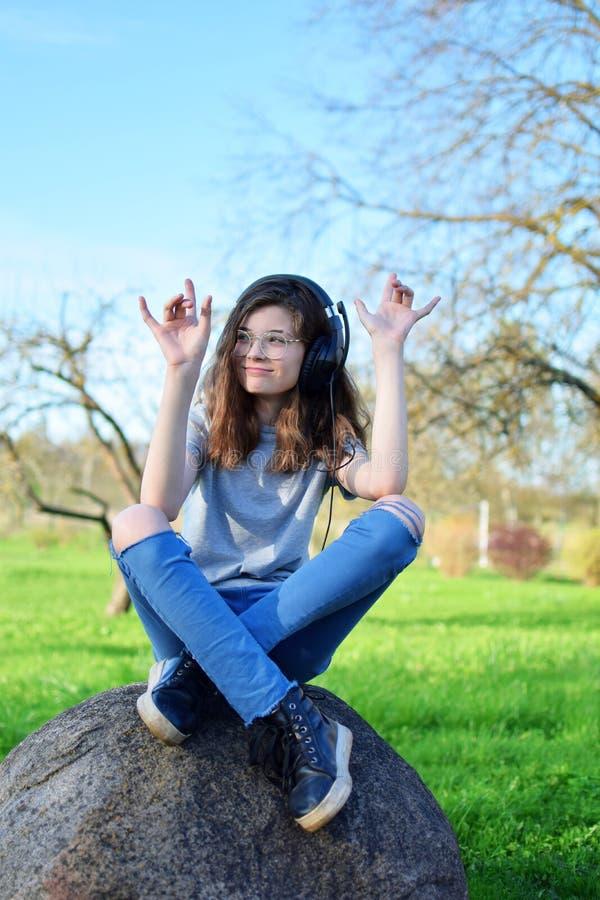 青少年的女孩听的音乐外面 免版税库存照片