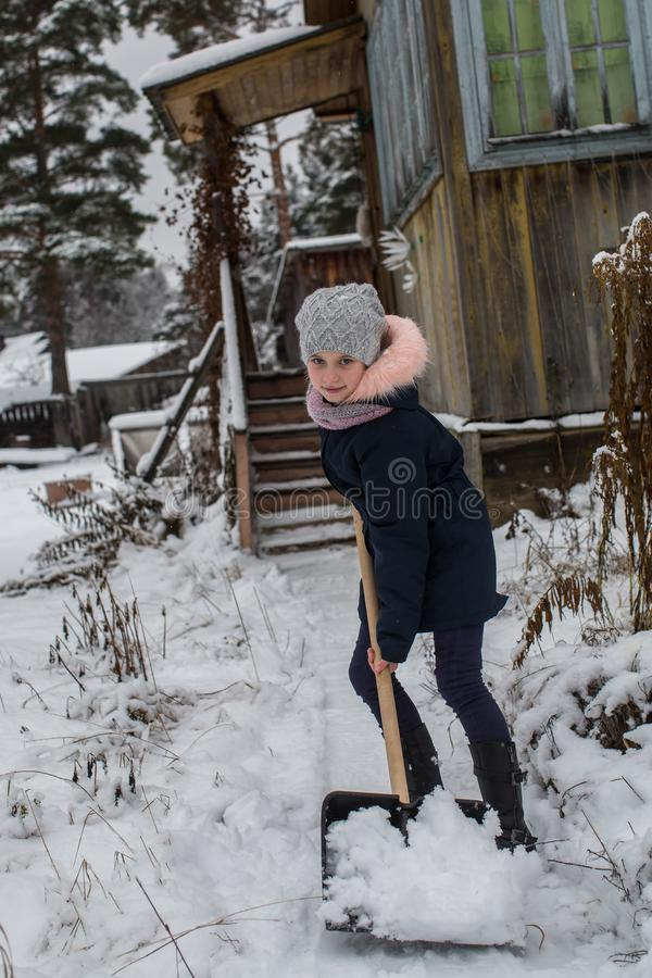 青少年的女孩在一个农村房子附近清洗雪 冬天 库存照片