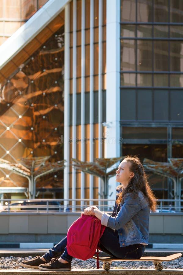 青少年的女孩坐与一个桃红色背包的一个冰鞋板在大城市 免版税库存图片