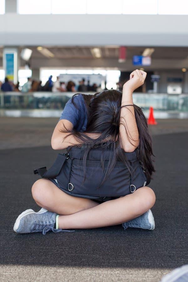青少年的女孩坐与行李的机场地板,睡觉 免版税库存图片
