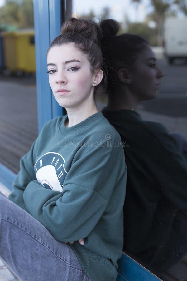 青少年的女孩坐的看往照相机 库存图片