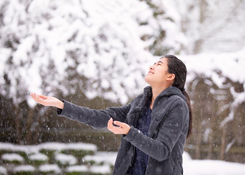 青少年的女孩户外胳膊在冬天伸出享受降雪 免版税库存照片