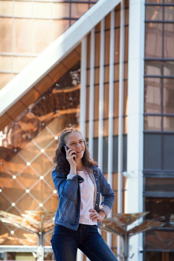 青少年的女孩有一次手机谈话在一个大大都会 库存照片