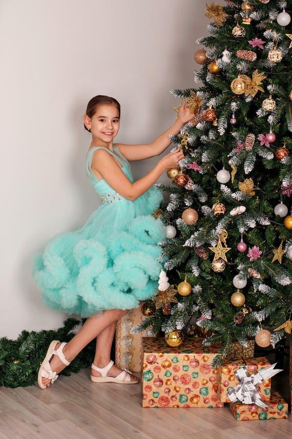 青少年的女孩用圣诞树玩具在蓝色豪华的礼服的新年树装饰 库存图片