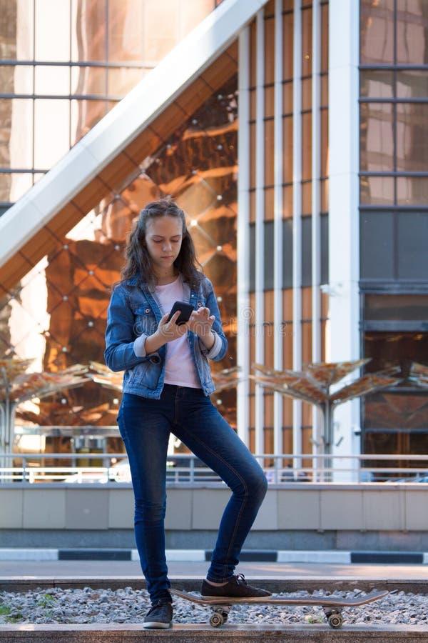 青少年的女孩看看一个智能手机在一个大大都会 免版税库存照片