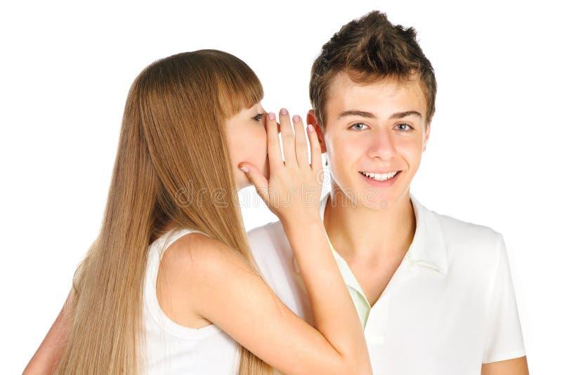青少年的女孩耳语在她的男朋友耳朵 库存图片