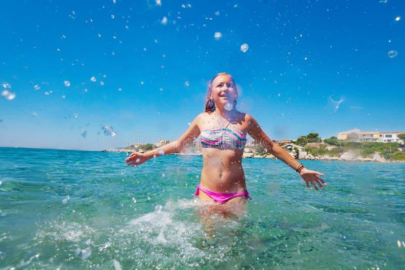 青少年的女孩获得使用的乐趣在浅水区 库存照片