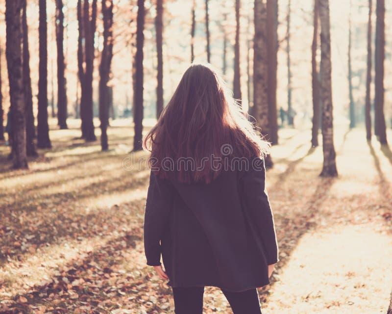 青少年的女孩身分在有她的秋天公园回到camer 免版税库存图片