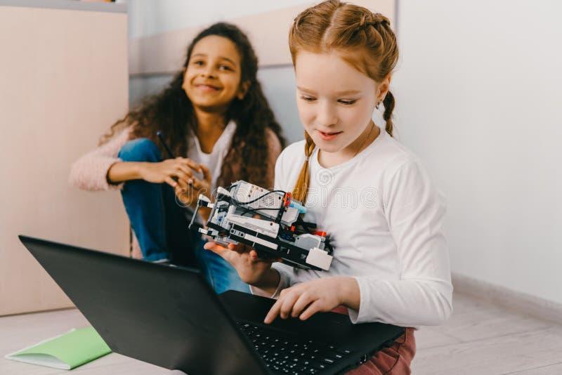 青少年的女小学生编程的机器人,当坐时 免版税库存图片