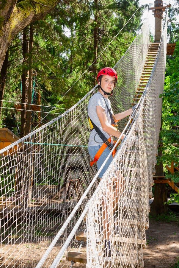 青少年的男孩佩带的安全设备输入绳索在树梢冒险公园追猎 免版税图库摄影