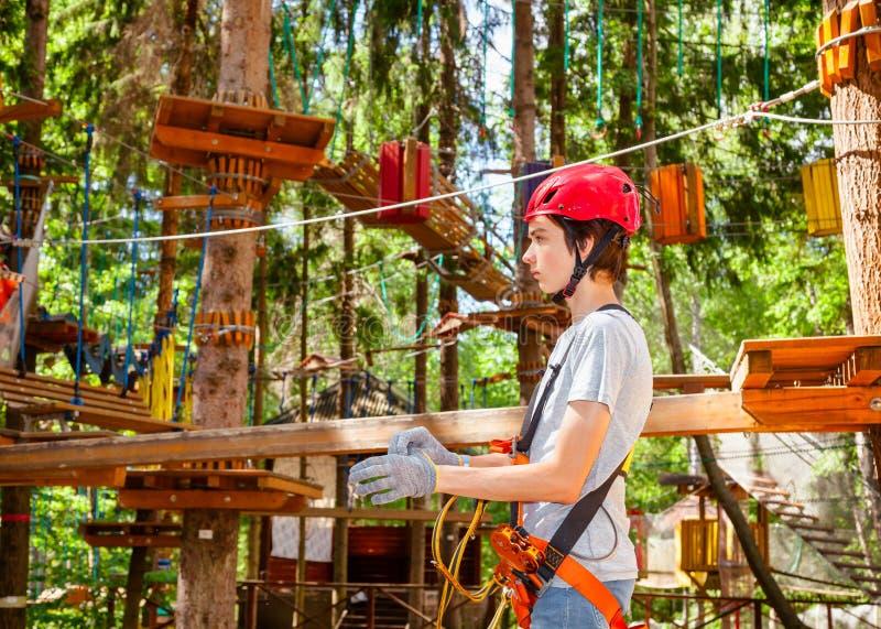 青少年的男孩佩带的自我保护安全设备输入绳索在树梢冒险公园追猎 库存图片