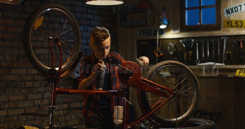 青少年的男孩修理骑自行车 免版税图库摄影
