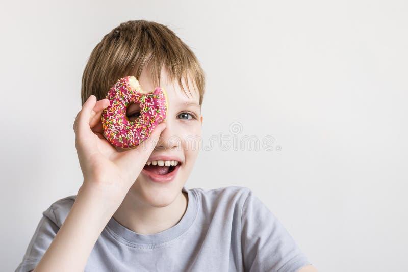 青少年的男孩调查被咬住的多福饼和微笑乐趣 免版税库存照片