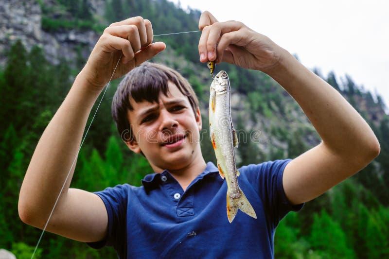 青少年的老化渔夫显示愉快,捉住嘉鱼属alpinus 图库摄影