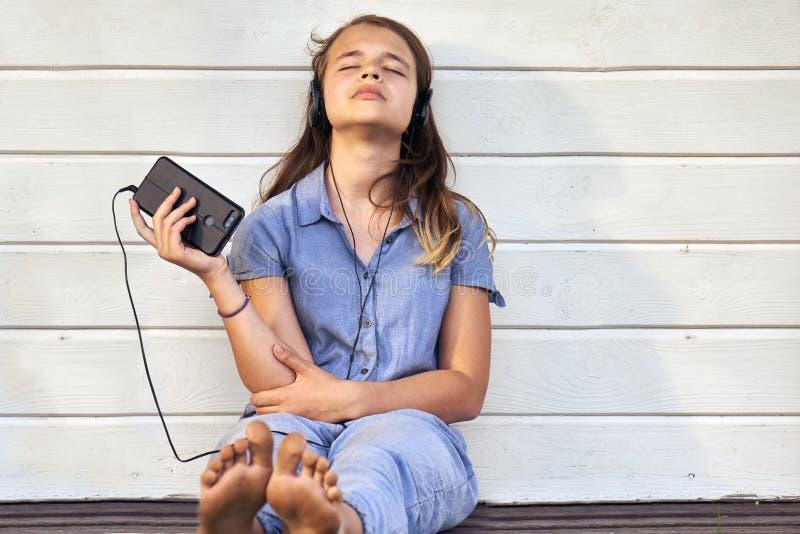 青少年的赤足享受从智能手机的音乐和唱歌户外在夏天晚上的女孩佩带的耳机 库存图片