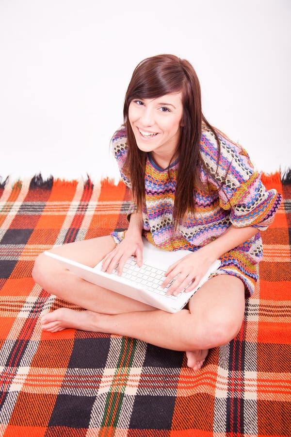 青少年美丽的棕色女孩的膝上型计算&# 免版税图库摄影
