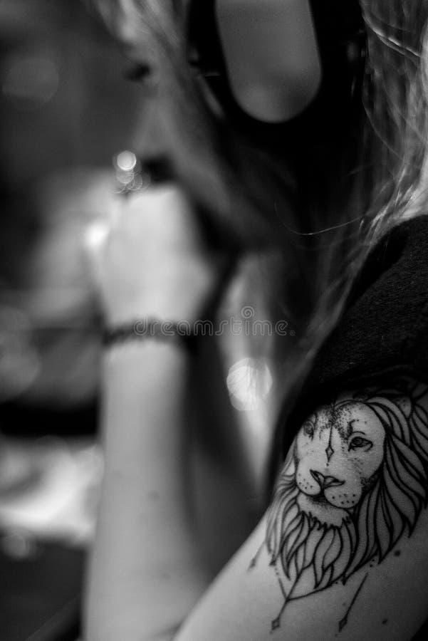 青少年与狮子Tatoo和耳机 库存照片