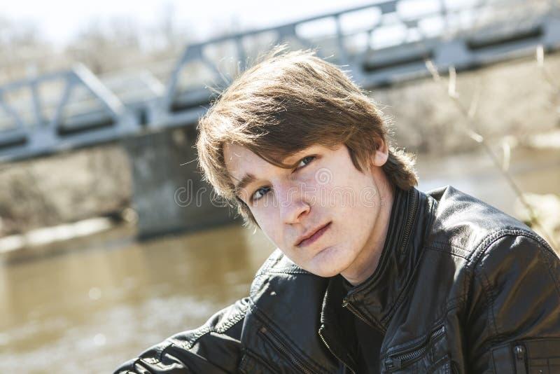青少年坐外面接近桥梁皮夹克 免版税库存图片