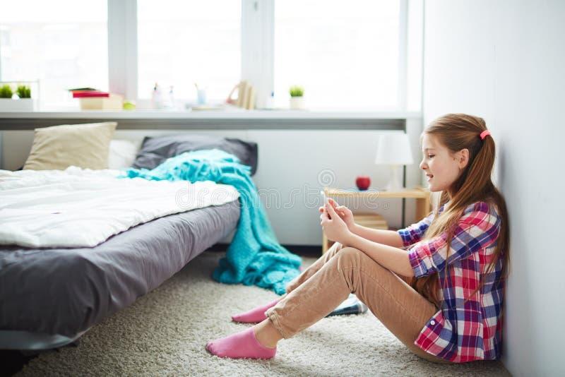 青少年女孩的smartphone 库存图片