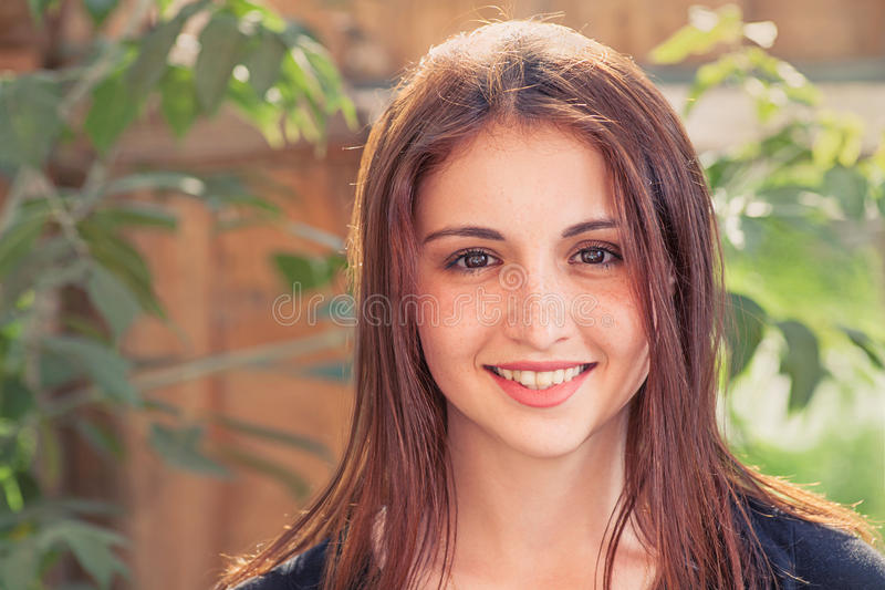 青少年微笑的红头发人 正面图一个微笑的十几岁的女孩的特写镜头图象户外反对与叶子的老木板条背景 免版税库存照片