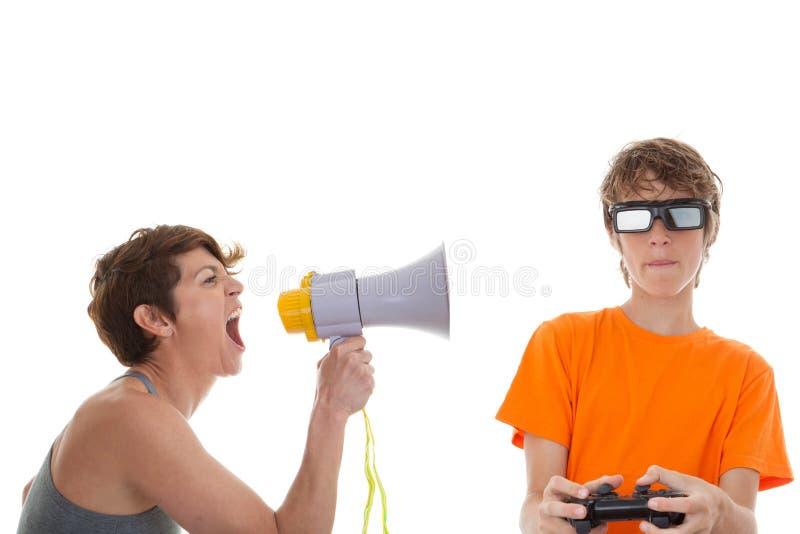 青少年的使用的计算机游戏的恼怒的母亲 免版税库存照片