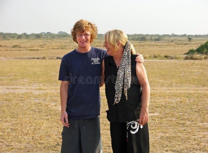 青少年的儿子和更旧成熟母亲笑愉快在徒步旅行队非洲 库存图片