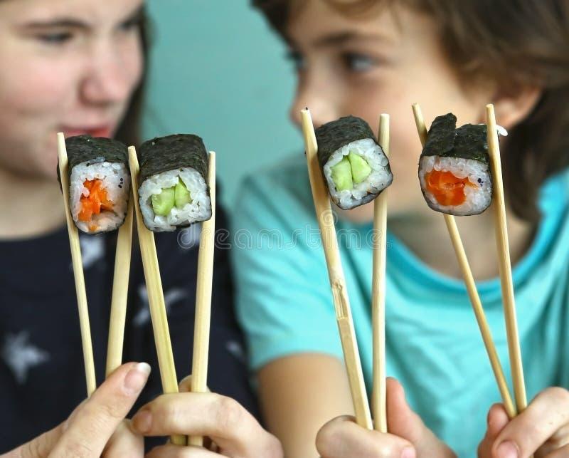 青少年的兄弟姐妹男孩和与寿司卷的女孩孩子 免版税库存照片