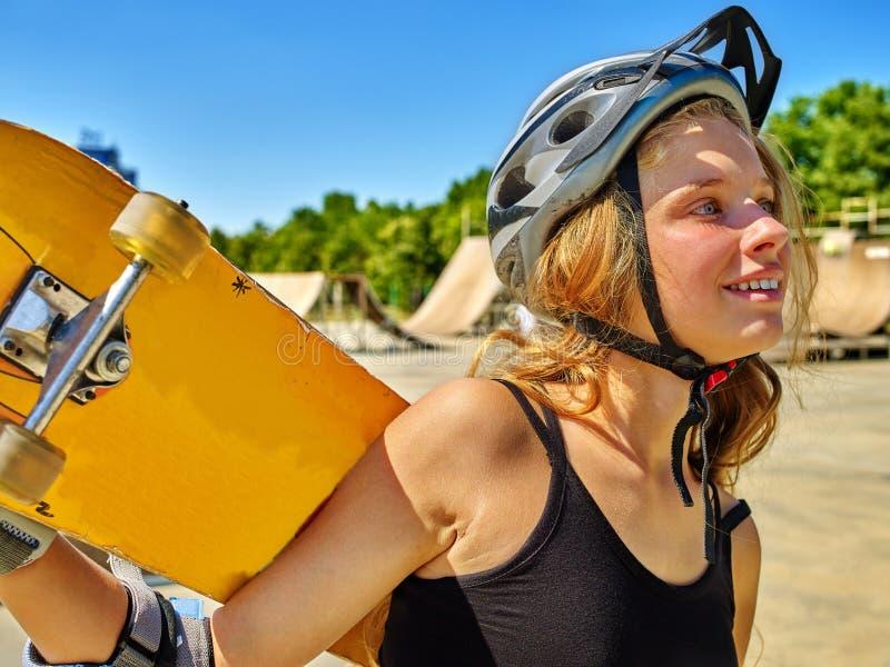 青少年的女孩乘坐他的滑板 库存图片