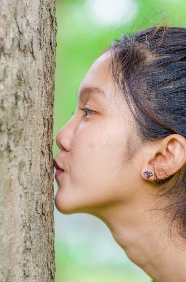 青少年的女孩亲吻树 库存图片