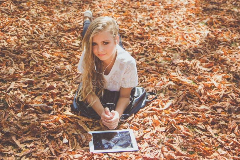 青少年的女孩在有个人计算机的秋天公园 库存图片