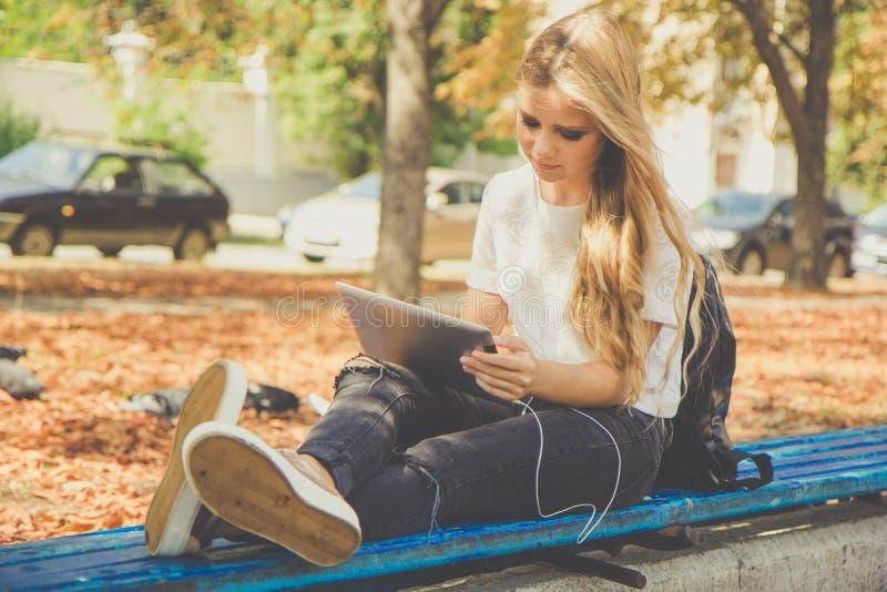 青少年的女孩在有个人计算机的秋天公园 库存照片