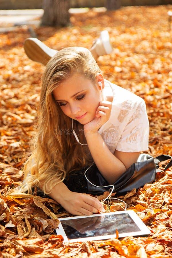 青少年的女孩在有数字式片剂的秋天公园 图库摄影
