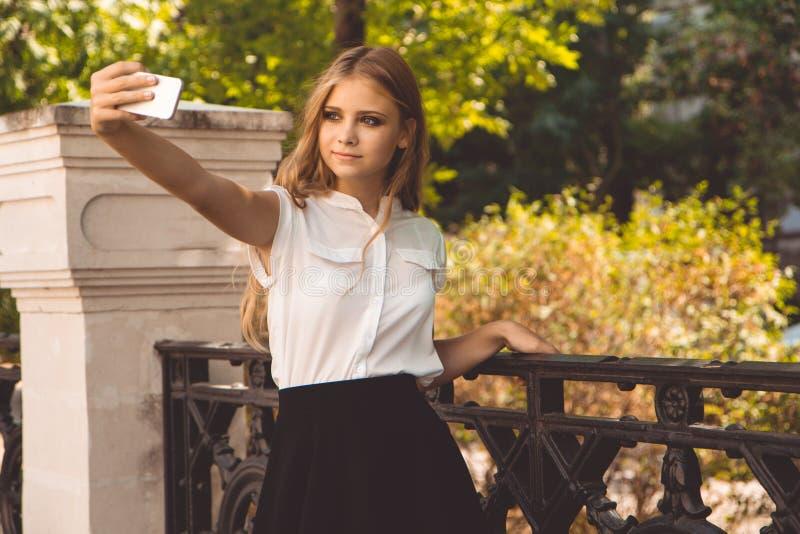 青少年的女孩在秋天公园采取selfie 库存照片
