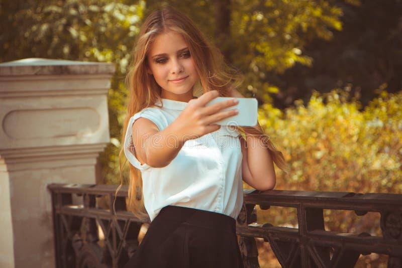 青少年的女孩在秋天公园采取selfie 免版税图库摄影