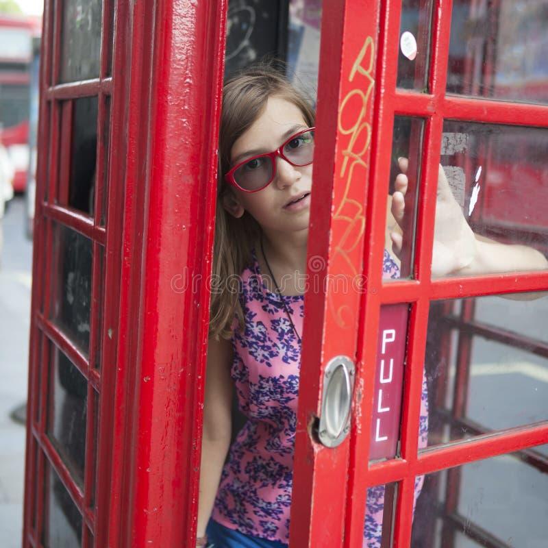 青少年的女孩在红色电话亭 免版税库存照片