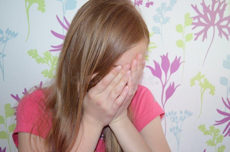 青少年的女孩用人工盖她的面孔 免版税库存照片