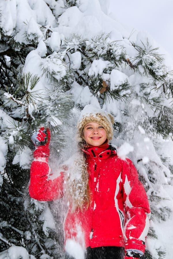 青少年的女孩站立反对积雪的冷杉木 免版税库存图片