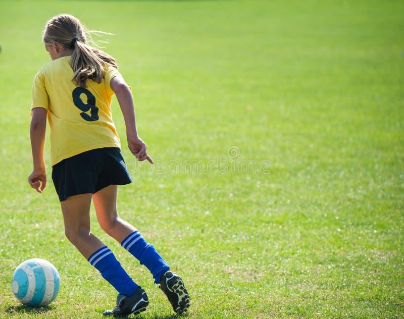 青少年的女孩足球运动员 免版税库存图片