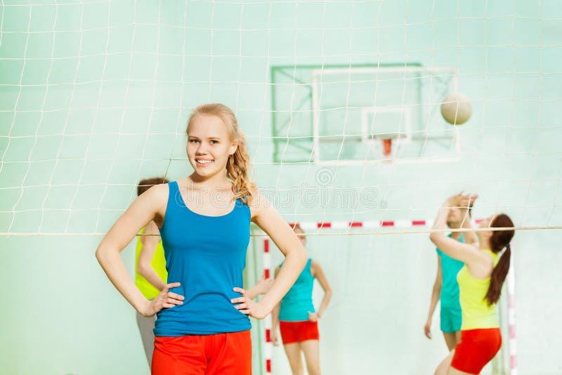 青少年的女孩,站立在健身房的排球运动员 免版税库存照片
