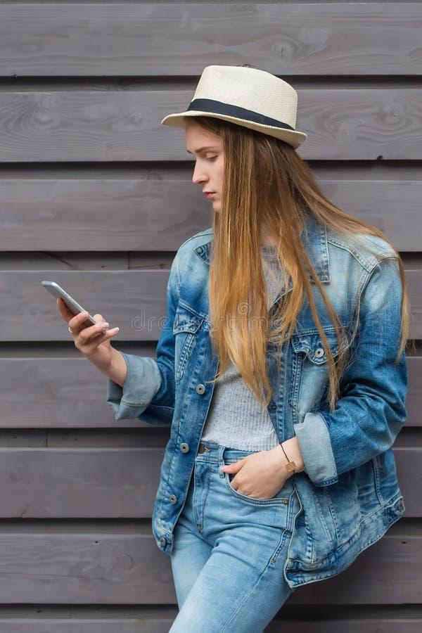 青少年的妇女智能手机在木墙壁外 免版税库存照片
