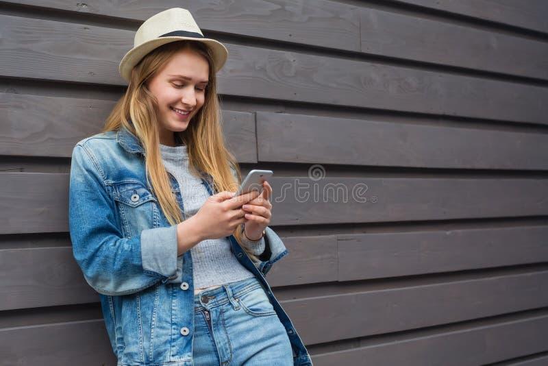 青少年的妇女智能手机在木墙壁外 库存照片