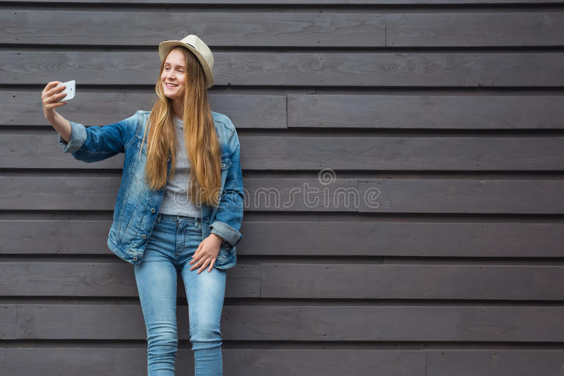 青少年的妇女智能手机得到selfie在木墙壁外 免版税库存照片