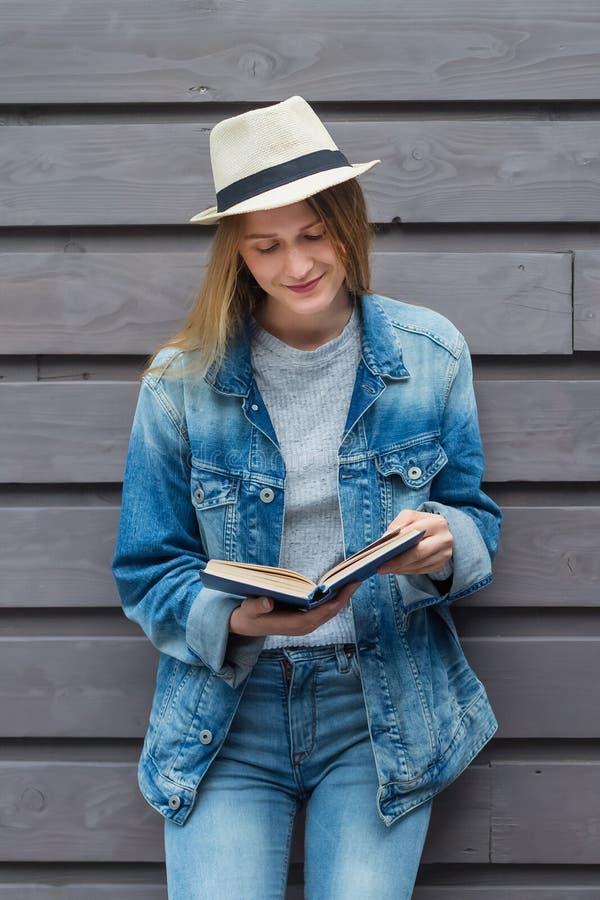 青少年的妇女读了书在墙壁外 免版税库存图片