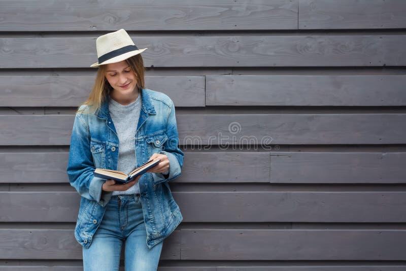 青少年的妇女读了书在墙壁外 免版税库存照片