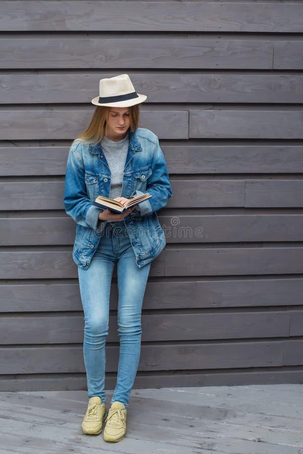 青少年的妇女读了书在墙壁外 库存图片