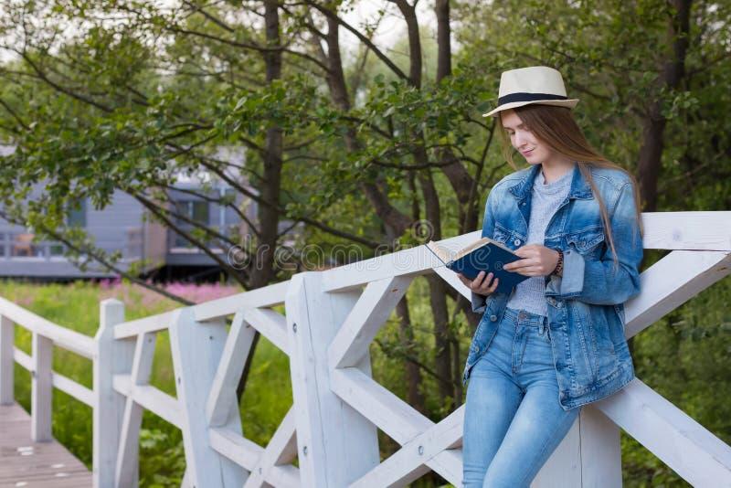 青少年的妇女读了书外面 库存照片