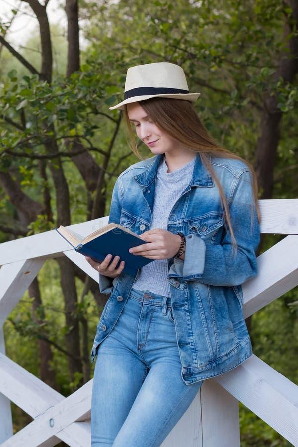 青少年的妇女读了书外面 免版税库存照片