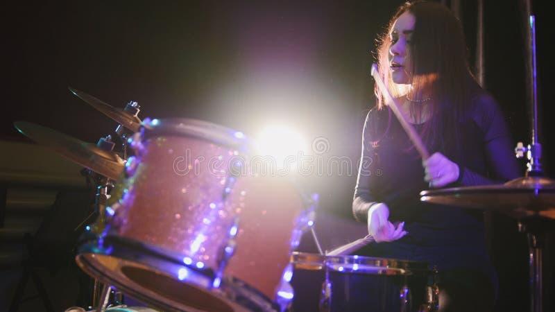 青少年的摇滚乐-有流动头发执行与鼓的撞击声鼓手的肉欲的女孩 免版税库存照片