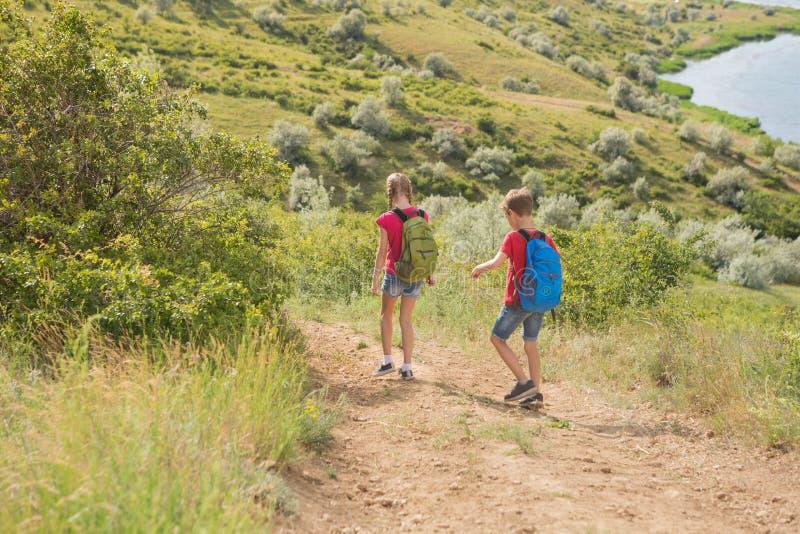 青少年的男孩和女孩有背包的在后面在远足,旅行,美好的风景去 库存图片