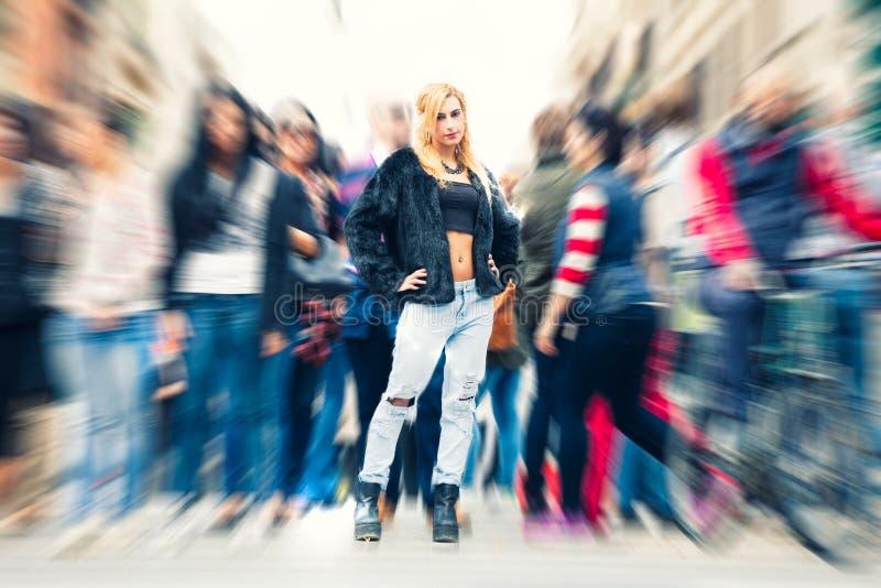 青少年的白肤金发的女孩在人群城市 都市街道城市生活 免版税库存图片
